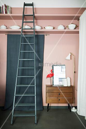 Stehlampe, Kommode und grüner Stoffbahn darüber Regal mit Porzellangeschirr und Leiter vor Rosa Wand