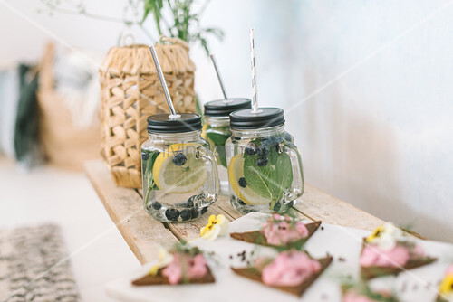 Triangular open faced sandwiches and flavoured water in mason jars with handles on buffet