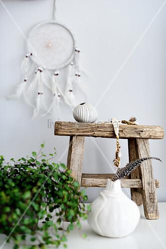 Weißer Traumfänger überm kleinen Holzhocker mit Boho-Deko