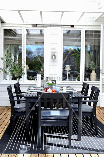 Gedeckter Tisch und schwarze Stühle auf der überdachten Terrasse