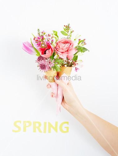Hand hält rosafarbene Blumensträußchen in zwei Eiswaffeln