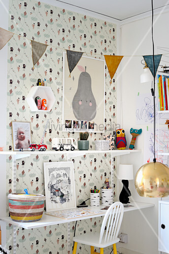 Regalsystem mit Schreibtisch an gemusterter Wand im Kinderzimmer
