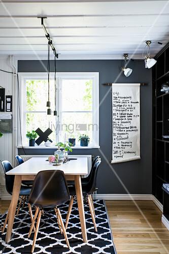 Tisch mit Klassikerstühlen im Essbereich mit schwarzen Wänden