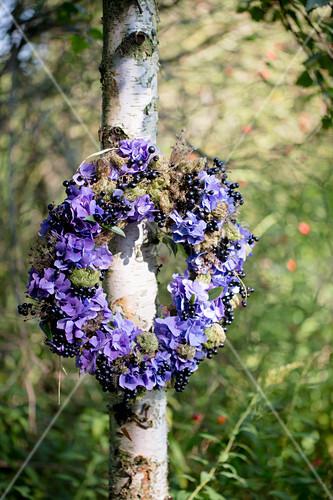 Wreath of purple hydrangeas and blackcurrants hung on tree