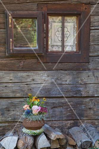 Herbstliches Blumengesteck in der Schale der Sapucaia-Nuss vor rustikalem Holzhaus