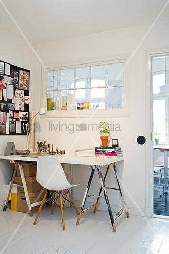 Schreibtisch aus Malerböcken und Tischplatte vor einem Innenfenster