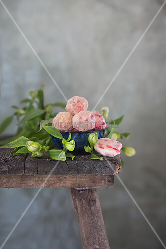 Dish of iced cheesecake truffles on wooden stool