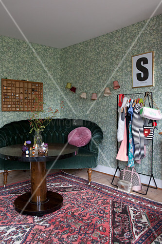 Round wooden table, velvet sofa and clothes rail against green wallpaper