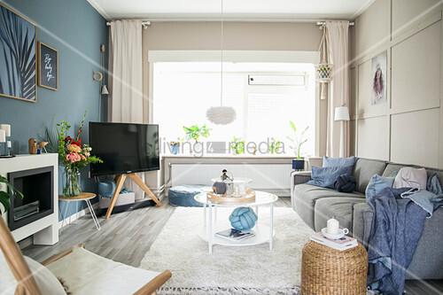 Wohnzimmer im skandinavischen Stil mit Wänden in Blau und Beige