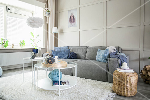 Grey sofa against beige panelled wall in bright living room