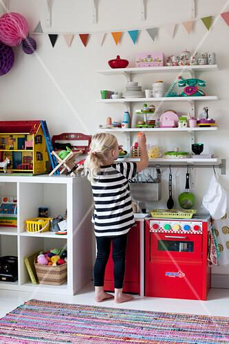 Blonde little girl in front of shelves in bedroom