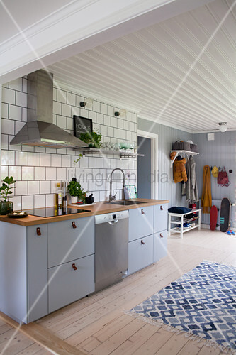 Grey kitchen counter against tiled wall, blue-and-white rug on pale wooden floor and coat rack in background