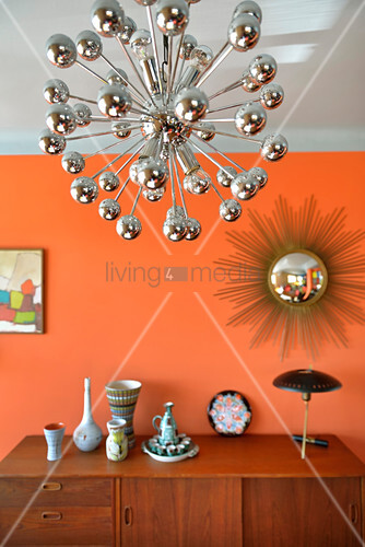 Sideboard below sunburst mirror on orange wall