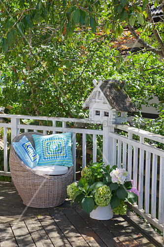 Blue-and-green cushions on round wicker chair on balcony