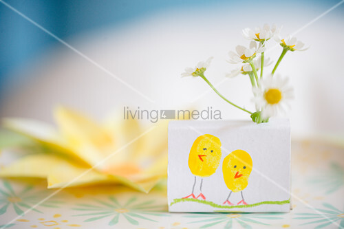 Chicks drawn on box holding flowers decorating table
