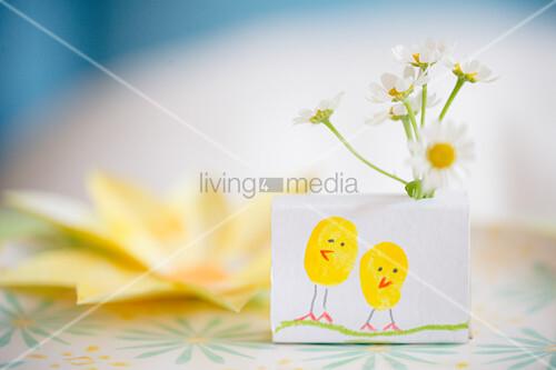 Mit Küken bemalte Schachtel mit Blumen als Tischdeko