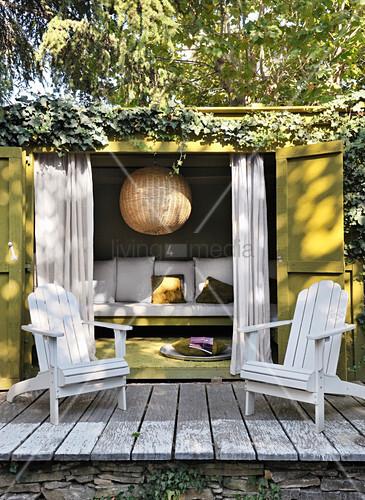 Zwei Deckchairs auf der Terrasse vor einem bewachsenen Gartenhaus