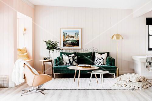 Grünes Sofa mit Dekokissen, Coffeetable und Drehsessel in Wohnzimmer mit weißer Holzverkleidung