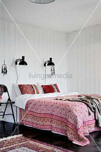 Floral cover on double bed below black reading lamps mounted on white wood-clad bedroom wall