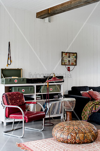 Suitcases and records on sideboard, red leather chair and leather pouffe in living room with white wood-clad walls