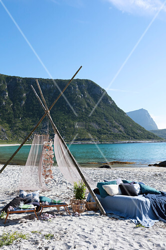 Wigwam decorated with shells and bed linen and pillows in shades of blue on bed on beach