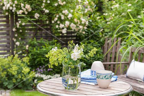 Strauß mit Frauenmantel und Akelei im Weckglas auf dem Gartentisch