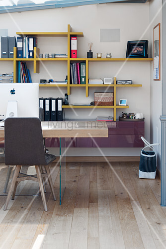 Desk with solid wooden top in front of wall-mounted shelves