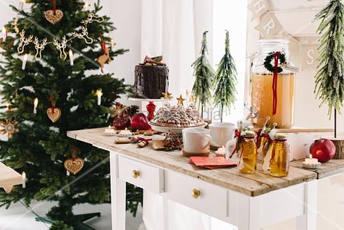 Desserttisch mit warmen Apfelpunsch, Gugelhupf und Dripping Cake, im Hintergrund Weihnachtsbaum