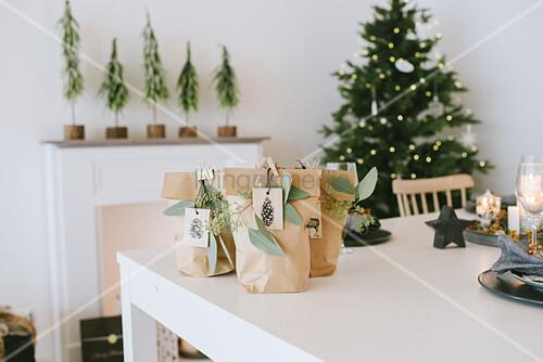 Weihnachtliche Geschenktüten aus braunem Papier auf weißem Tisch