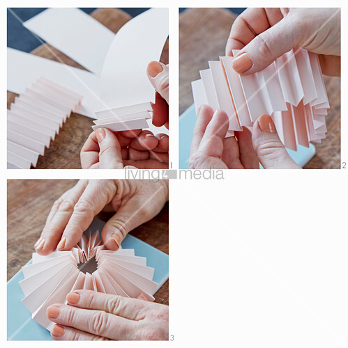 Hande falten eine Rosette aus rosafarbenem Papier