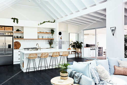 Cushions on sofa and white kitchen with island counter in open-plan interior