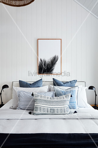 Blue bedspread on double bed with white wood-clad walls