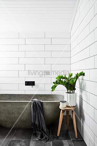 Concrete bathtub and houseplant on stool in white-tiled bathroom
