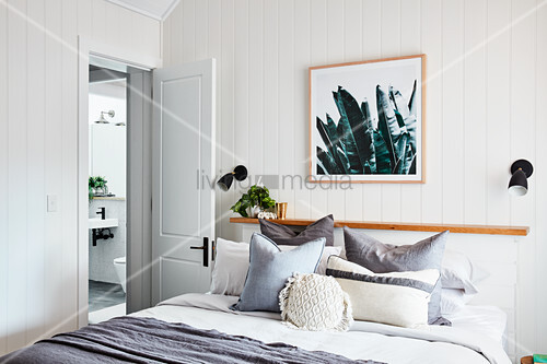 Scatter cushions on double bed against narrow shelf in bedroom with white wood-clad walls