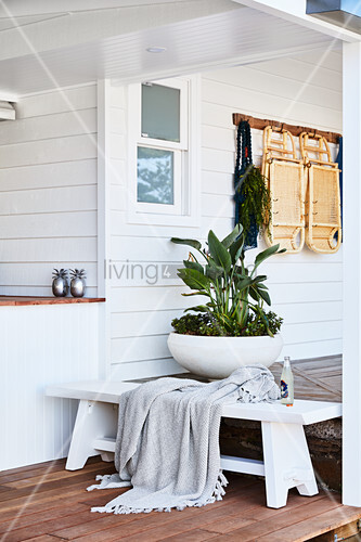 White wooden bench and planted bowl on veranda