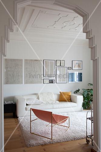 Blick ins Wohnzimmer mit weißer Ledercouch, darüber alte Skizzen an der Wand