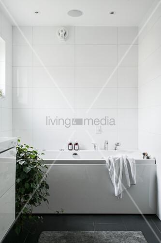 Bathtub in white bathroom with black floor