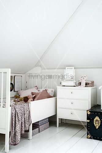 Vintage furnishings in child's white attic bedroom