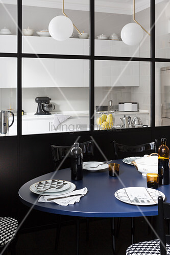 Dining table with blue top in front of glass partition looking into kitchen