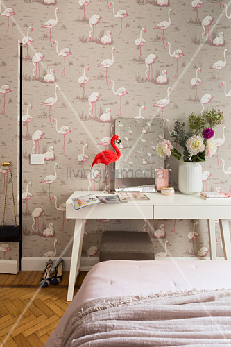 Flamingo ornament on table against flamingo-patterned wallpaper