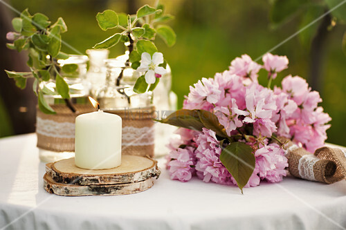 Candle on wooden coaster, cherry blossom and peonies on garden table
