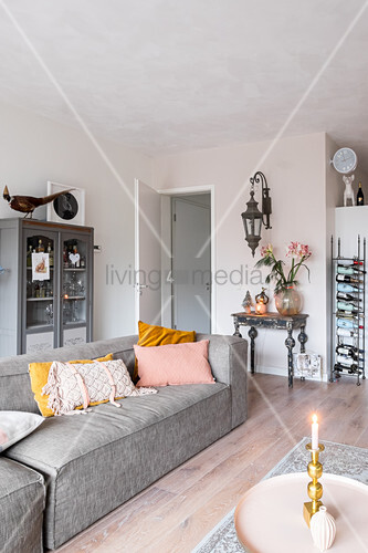 Grey sofa in front of glass-fronted cabinet in bright living room