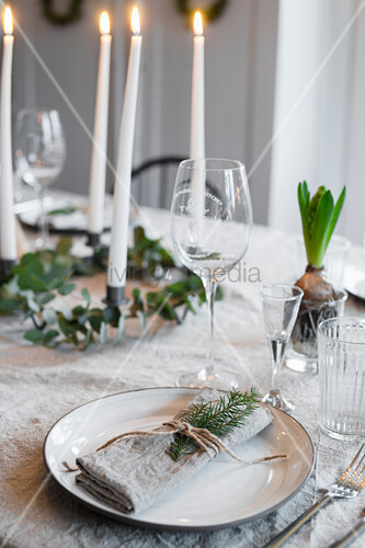 Linen napkin tied with fir sprig and spring on set table