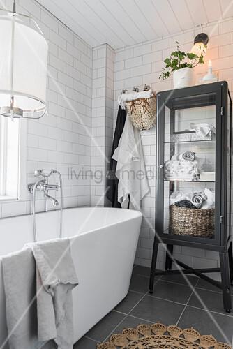 Vitrinenschrank neben der freistehenden Badewanne