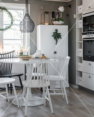Windsor chairs at dining table in grey-and-white kitchen-dining room