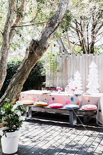 weihnachtlich gedeckter tisch mit holzbank auf sonniger terrasse bild kaufen living4media. Black Bedroom Furniture Sets. Home Design Ideas
