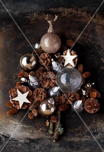 Weihnachtsdekoration aus Kugeln, Zapfen und Sternen in Tannenbaumform