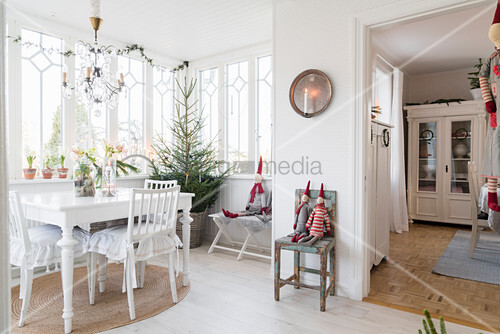 White table and chairs in festively decorated conservatory