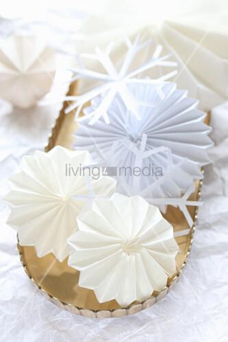 Sterne und Schneeflocken aus weißem Papier im goldenen Tablett