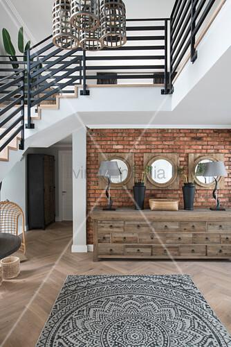 Kommode vor Backsteinwand unter der Treppe im offenen Wohnraum